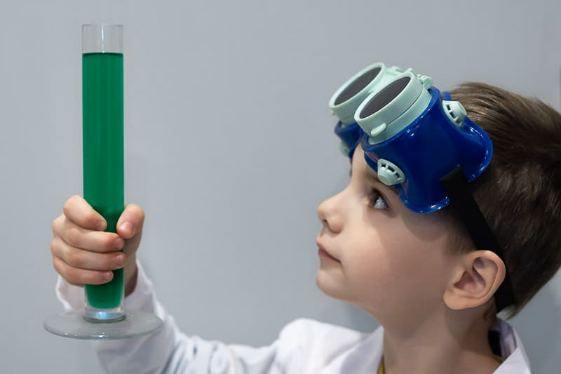 boy in labcoat and goggles with test tube science experement
