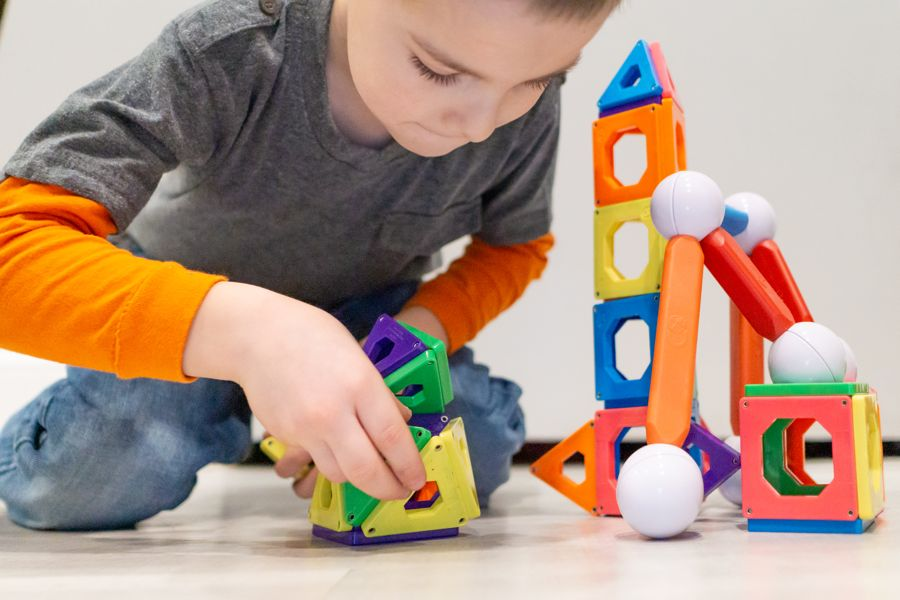 Boy playing with Magna Tiles STEM toy