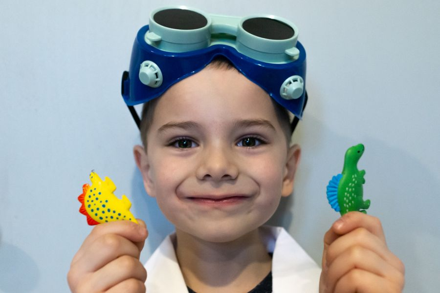 young scientist boy holding toy dinosaurs